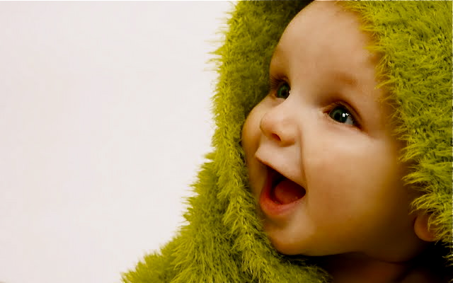 A beautiful smiling baby wrapped in a furry green blanket